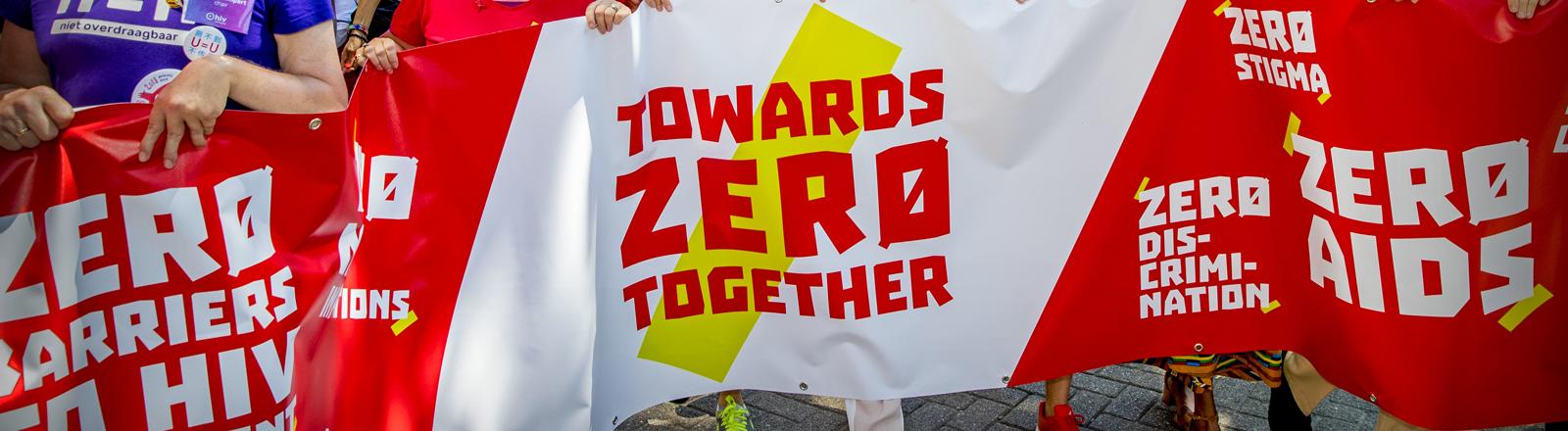 """Auf einem Protestmarsch in Amsterdam anlässlich der Weltaidskonferenz tragen Protestierende ein rot-weißes Banner auf dem """"Towards Zero Together"""" steht."""