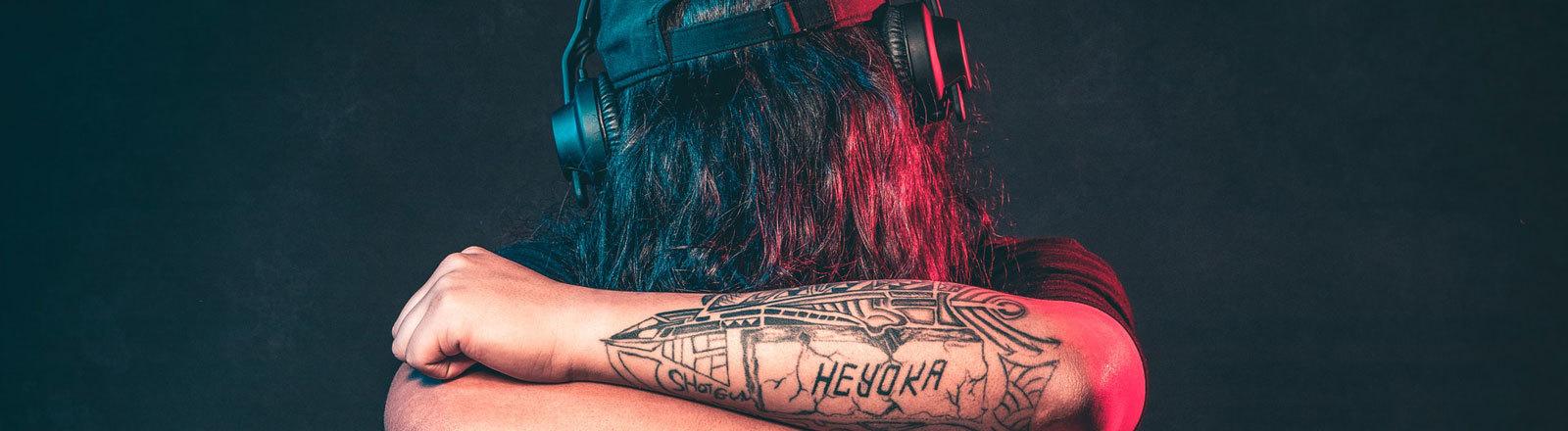 Typ mit Kopfhörer und Tattoo