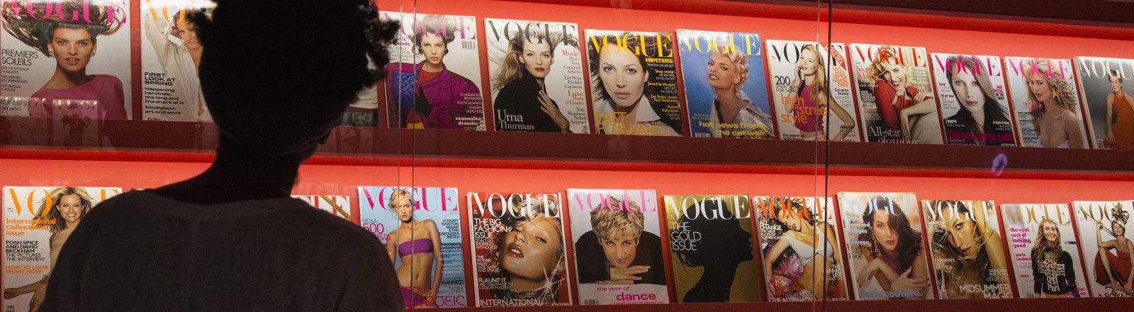 Frau steht vor Aufsteller mit Vogue-Ausgaben Cover