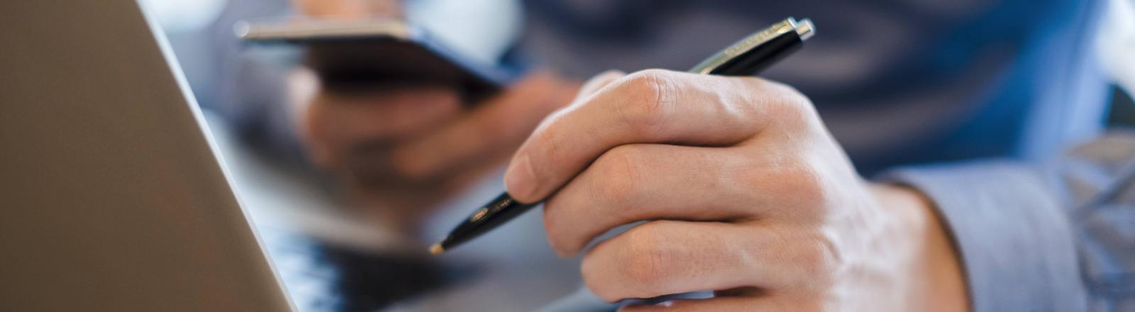 Ein Mann sitzt vor seinem Laptop und hält in der Linken Hand einen Kugelschreiber und mit der rechten sein Smartphone