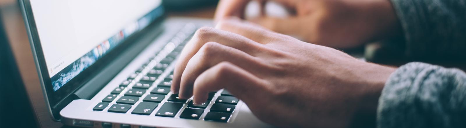 Nahaufnahmen von Händen auf der Tastatur eines Apple Laptops