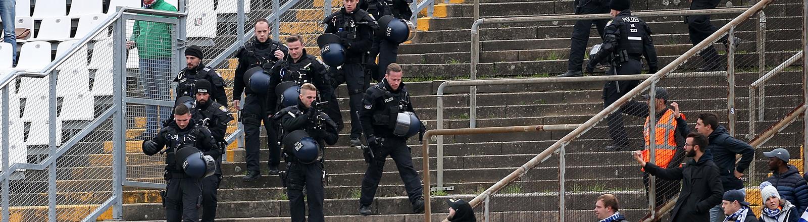Nachdem Kieler Hooligans versucht haben den Darmstädter Block zu stürmen, schreitet die Polizei ein und geht in den Kieler Block um die Lage zu beruhigen.