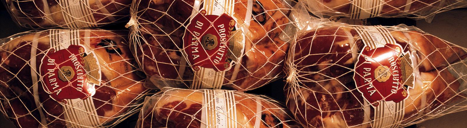 Mehrere Parmaschinken liegen nebeneinander. Sie sind, wie es typisch ist für den Schinken, in Netzen verpackt. Auf Etiketten steht das Wort Parma; Foto: dpa