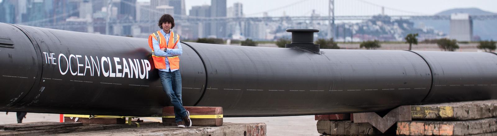 Boyan Slat ist der Gründer von The Ocean Cleanup. Er lehnt an einer langen, schwarzen Röhre, die Teil der Filteranlage ist, um Plastikkmüll aus dem Meer zu fischen. Im Hintergrund ist eine Skyline zu sehen.