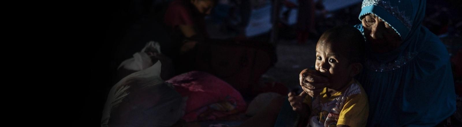 Eine Großmutter versorgt ihr Enkelkind in Indonesien nach der Tsunami-Katastrophe.