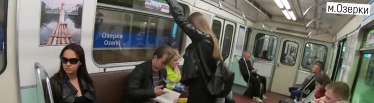 Screenshot eines Videos: Eine Frau in der U-Bahn gießt einem sitzenden Mann aus einer Flasche Flüssigkeit in den Schritt.