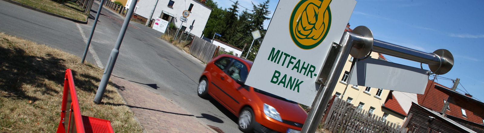 Eine rote Bank steht in der Ortsmitte der Gemeinde Oberlödla im Altenburger Land. Es ist eine Mitfahrbank. An einem Schild hängt ein Hinweis; Foto: dpa