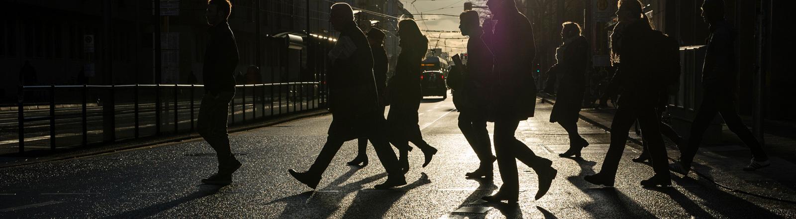 Fußgänger überqueren in Berlin im Gegenlicht der Sonne eine Straße (24.02.2016); Foto: dpa