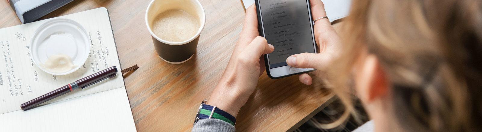 Eine Frau mit Smartphone und Kaffee am Schreibtisch