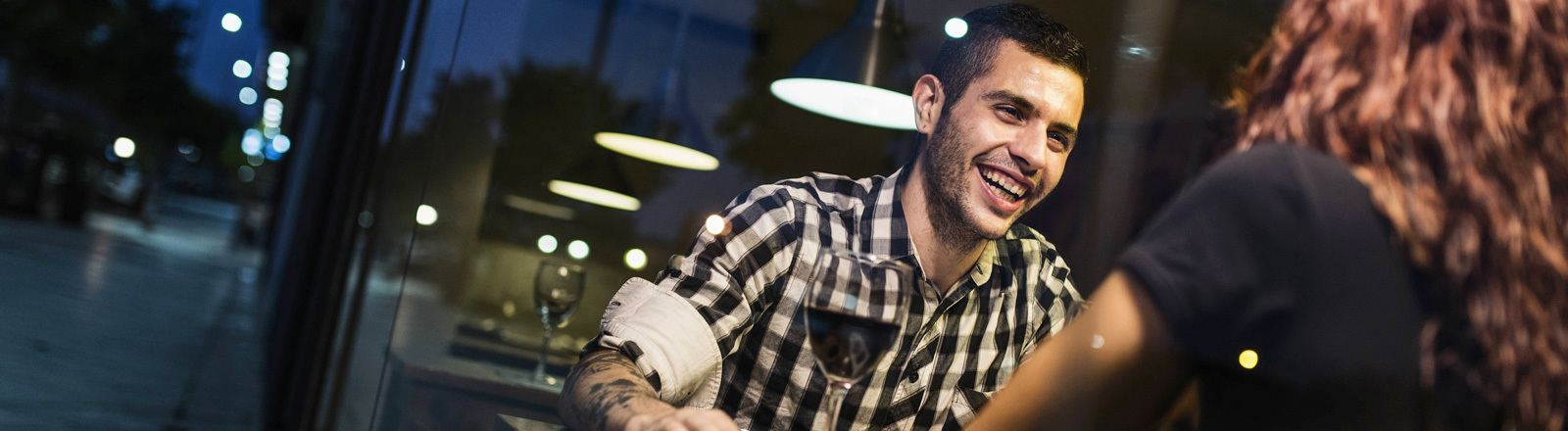 Ein Mann und eine Frau sitzen sich in einem Restaurant an einem Tisch gegenüber. Sie ist von hinten zu sehen. Er lacht sie an.