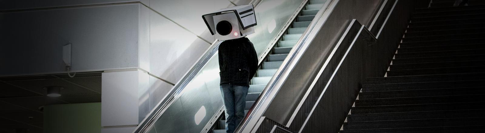Ein Mensch mit einer Überwachungskamera aus Pappe über dem Kopf