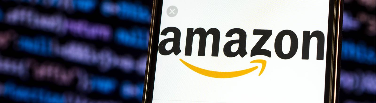 Im Vordergrund ein Smartphone mit Amazon-Logo auf dem Bildschirm, im Hintergrund verschwommen Datenkolonnen