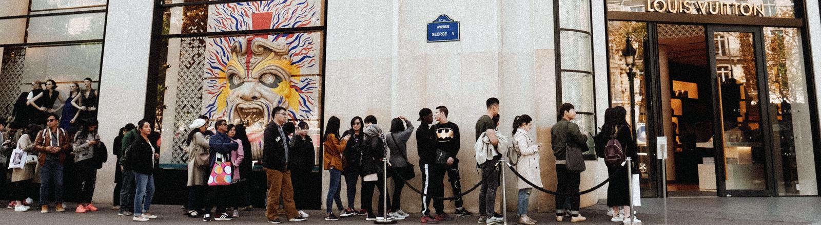 Menschen stehen Schlange vor einer Louis Vuitton Filiale