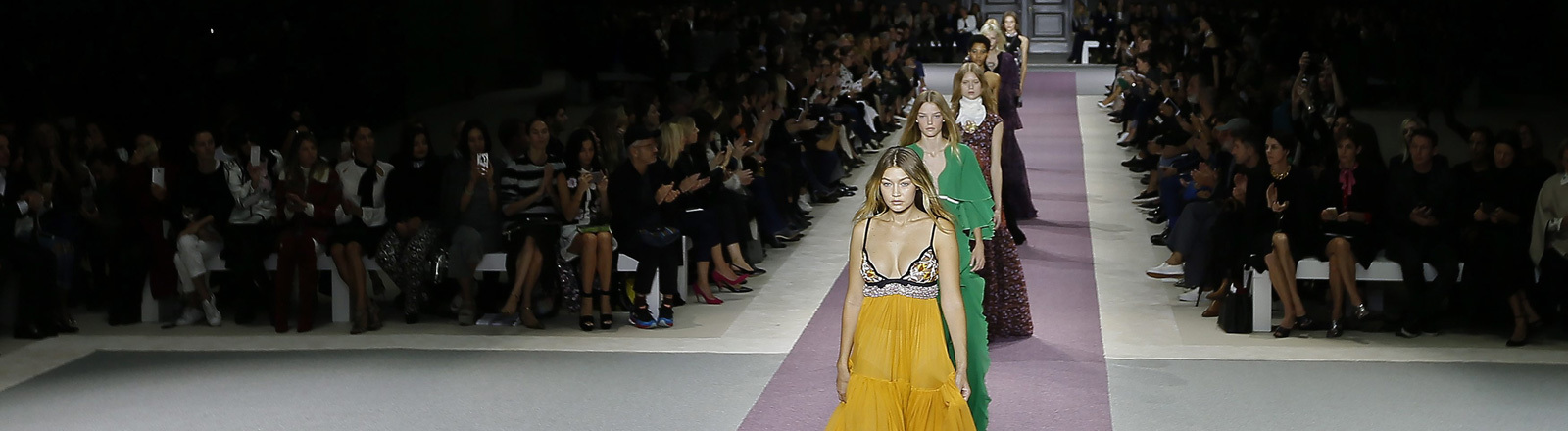 Bei der Fashions Week in Paris (Oktober 2015) laufen verschiedene Model. Als erste Gigi Hadid. Links und rechts sitzt zahlreiches Publikum.
