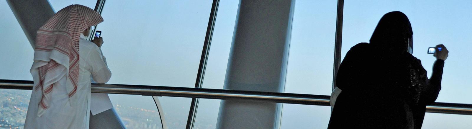 Auf einer Aussichtsplattform im saudi-arabischen Riad stehen eine Frau und ein Mann. Sie schauen beide auf ihre Mobiltelefone.