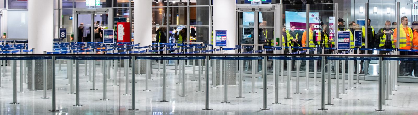 Am Flughafen Düsseldorf ist der Bereich der Sicherheitskontrollen komplett menschenleer. Im Hintergrund stehen Personen mit Warnwesten. Es sind Streikende. Die Gewerkschaft Verdi hat am 10.01.2019 zu einem Warnstreik aufgerufen; Foto: dpa