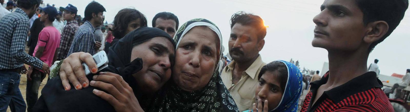 Nach einem Brand am 11.09.2012 in einer Textilfabrik im pakistanischen Karatschi stehen Angehörige zusammen. Eine Frau weint. Bei dem Feuer starben 250 Menschen.