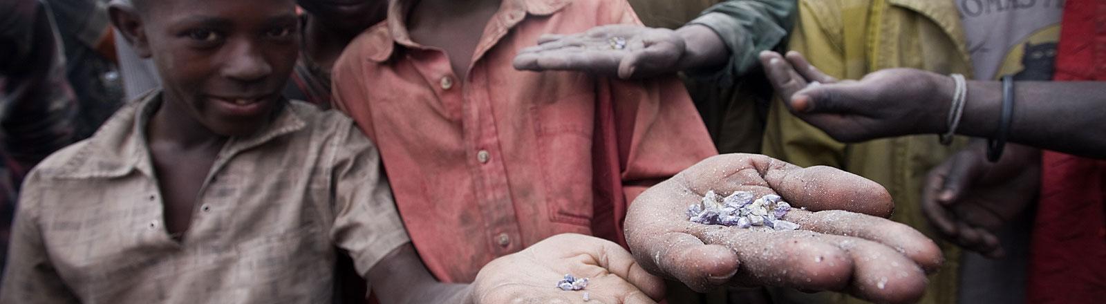 Afrikanische Bergarbeiter zeigen gefundene Edelsteine.
