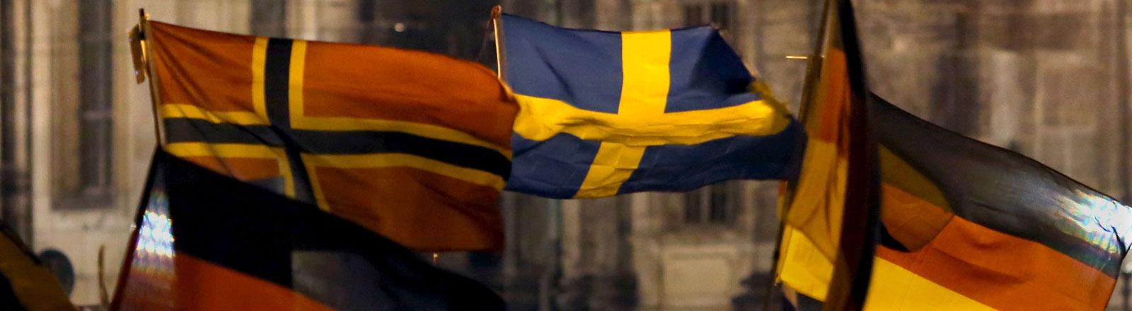 Anhänger des «Pegida»-Bündnisses (Patriotische Europäer gegen die Islamisierung des Abendlandes) demonstrieren am 22.12.2014 in Dresden (Sachsen) gegen die angebliche Überfremdung durch Flüchtlinge und schwenken Deutschlandfahnen. Auch eine norwegische und eine schwedische Flagge sind zu sehen.