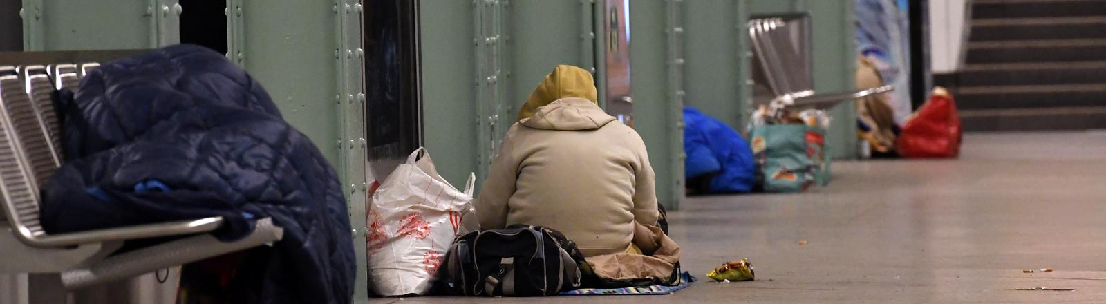Obdachlose sitzen und liegen in einem Berliner U-Bahnhof