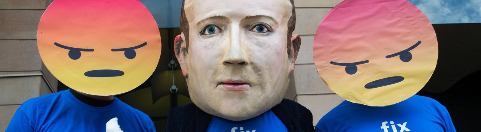 """Ein Mensch mit Mark Zuckerberg Maske, flankiert von zwei Menschen mit Wutsmiley-Masken. Alle tragen ein T-Shirt mit der Aufschrift """"fix fakebook"""""""