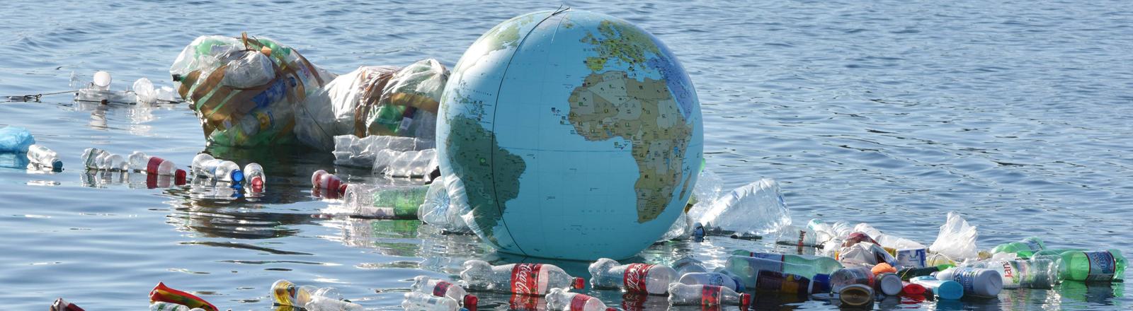 Eine Installation im Meer aus Plastikflaschen, Plastikmüll und einer Plastikweltkugel