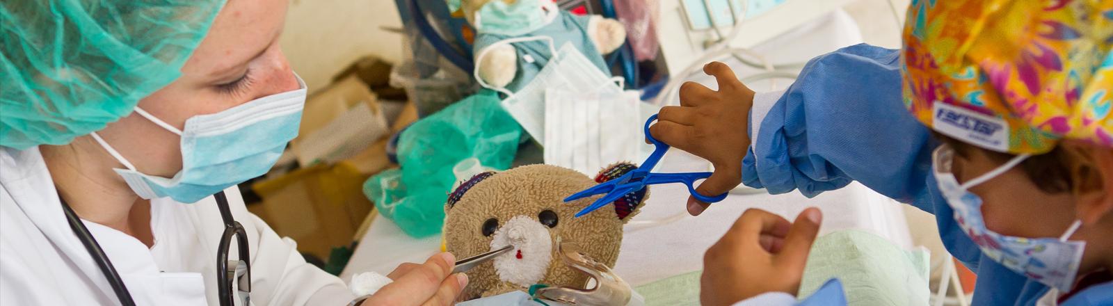 """Eine junge Frau und ein Kind, beide in OP-Kitteln mit Hauben """"operieren"""" einen Teddybär"""