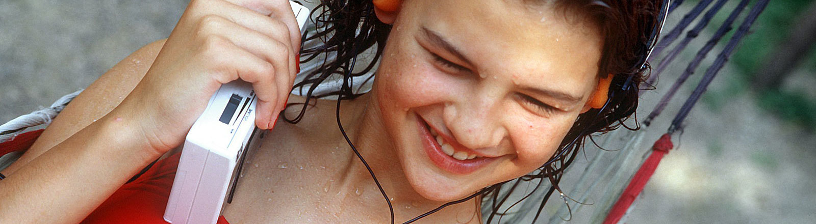 Eine junge Frau liegt in einer Hängematte und hört Musik mit ihrem Walkman. Aufnahme von 1986; Foto: dpa