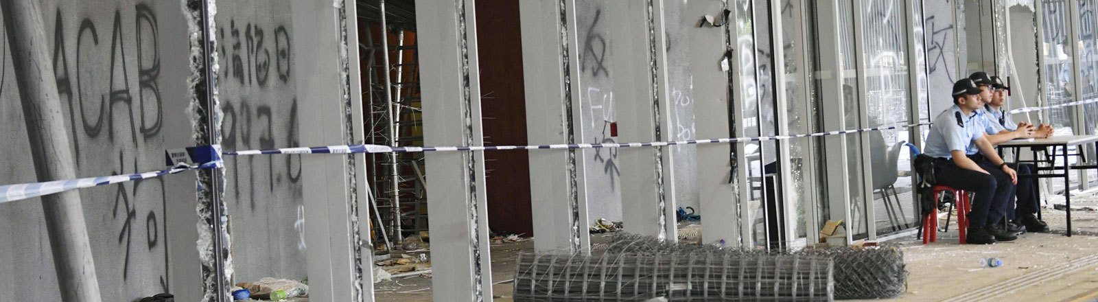 Das Parlamentsgebäude in Hongkong wurde nach Protesten schwer beschädigt. Fenster und Türen sind eingeschlagen. Davor sitzen drei Polizisten.