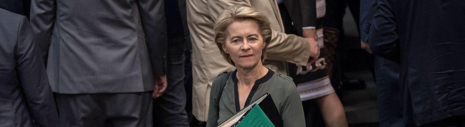 Bei einer Sitzung des deutschen Bundestags (28.06.2019) steht Verteidigungsministerin Ursula von der Leyen zwischen anderen Politikern.