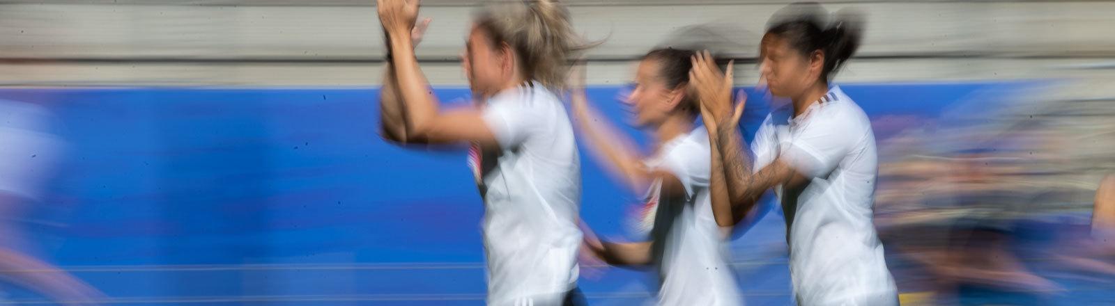 Drei Spielerinnen der Deutschen Fußball-Nationalmannschaft laufen beim Spiel Deutschland - Schweden über den Platz. Sie sind unscharf - klatschen beim Laufen in die Hände.
