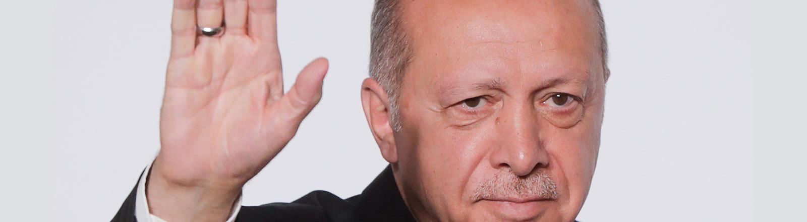 Der türkische Präsident Erdogan hebt die Hand zum Gruß.