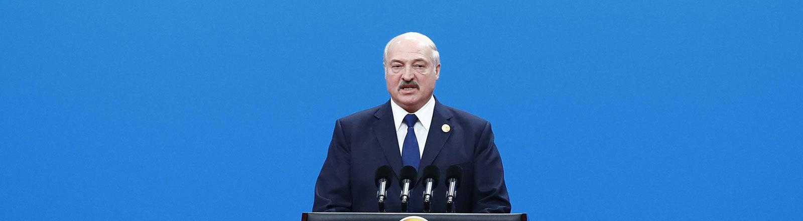 Der weißrussische Präsident Alexander Lukaschenko vor blauem Hintergrund an einem Rednerpult.