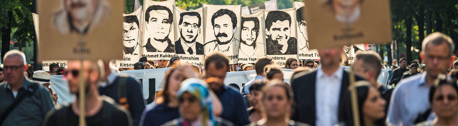 Demonstranten halten bei einer Kundgebung Schilder mit Porträt Abbildungen der NSU-Opfer. In München war am Morgen des 11.7.2018 der Prozess gegen den rechtsterroristischen NSU mit Schuldsprüchen zu Ende gegangen.