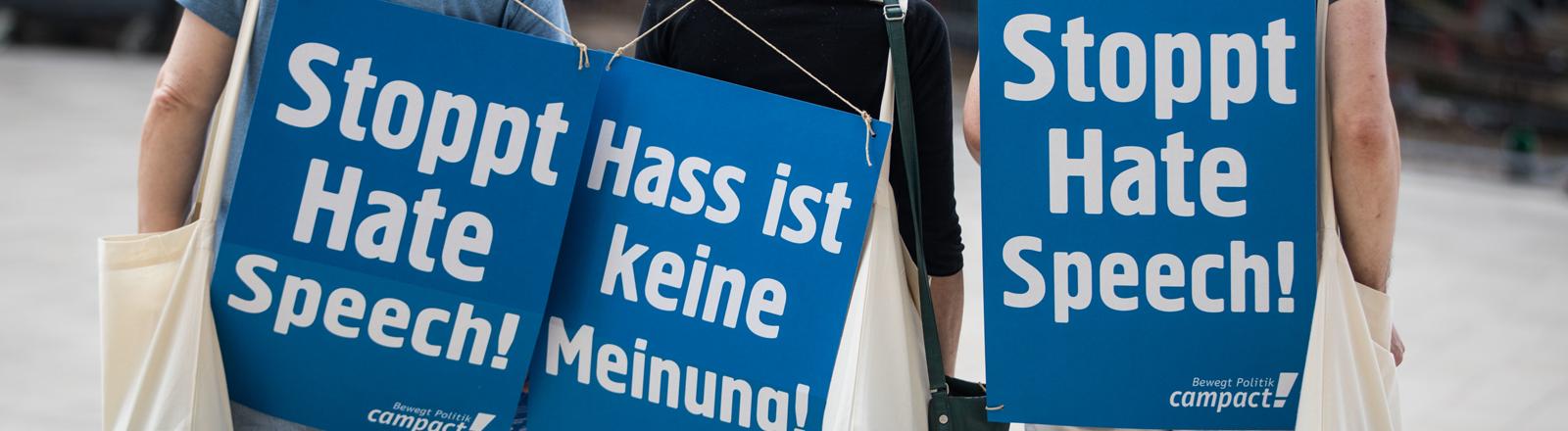 """Demonstrierende in Hessen tragen Plakate auf dem Rücken auf denen """"Stoppt Hate Speech"""" und """"Hass ist keine Meinung"""" steht."""