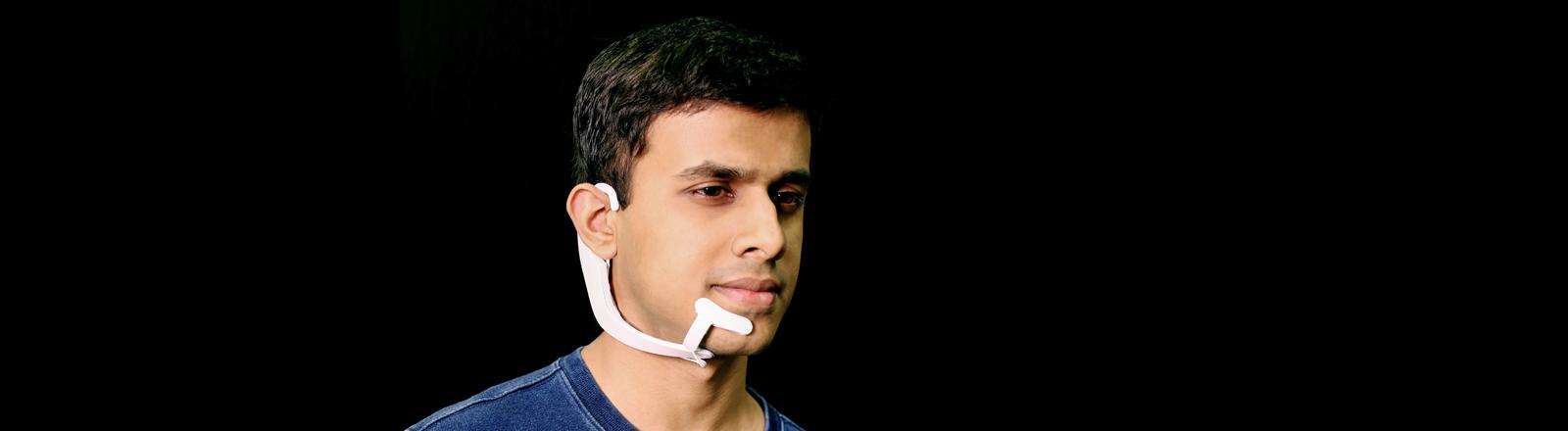 Arnav Kapur trägt sein Gerät mit dem Namen Alter Ego, ein weißer Bügel, der hinter dem linken Ohr beginnt und am Hals entlang bis zum Kinn reicht.