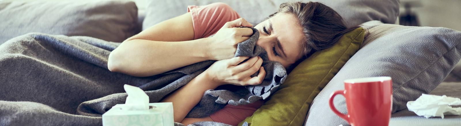 Eine junge Frau liegt auf dem Sofa, hält sich die Decke vors Gesicht, im Vordergrund eine Teetasse und eine Taschentuchbox