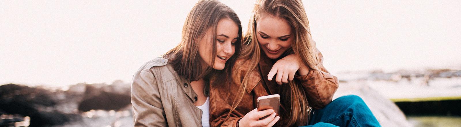 Zwei Mädchen schauen auf ein Smartphone