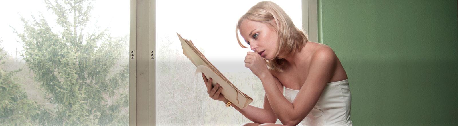 Eine Frau hockt vor einem Fenster und liest einen Stapel Papiere.