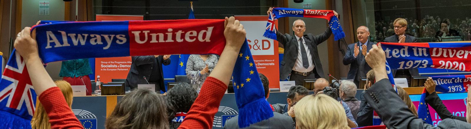 """29.01.2020, Belgien, Brüssel: Richard Corbett, (hinten 3.v.r) Vorsitzender der Labour Abgeordneten im Europaparlament, hält nach einer Fraktionssitzung einen Schal mit der Aufschrift """"Always United"""" hoch."""