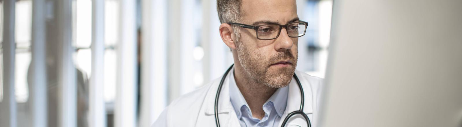 Arzt sitzt am Schreibtisch und schaut auf einen Computerbildschirm