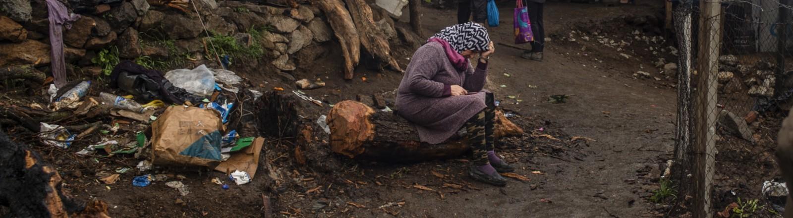 Griechenland, Lesbos: Eine Frau sitzt auf einem Baumstamm in einem Zwischenlager neben dem Lager Moria.