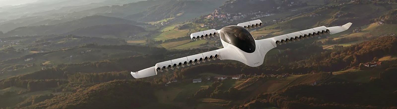 Der Prototyp Lilium fliegt über eine Landschaft mit vielen Hügeln.