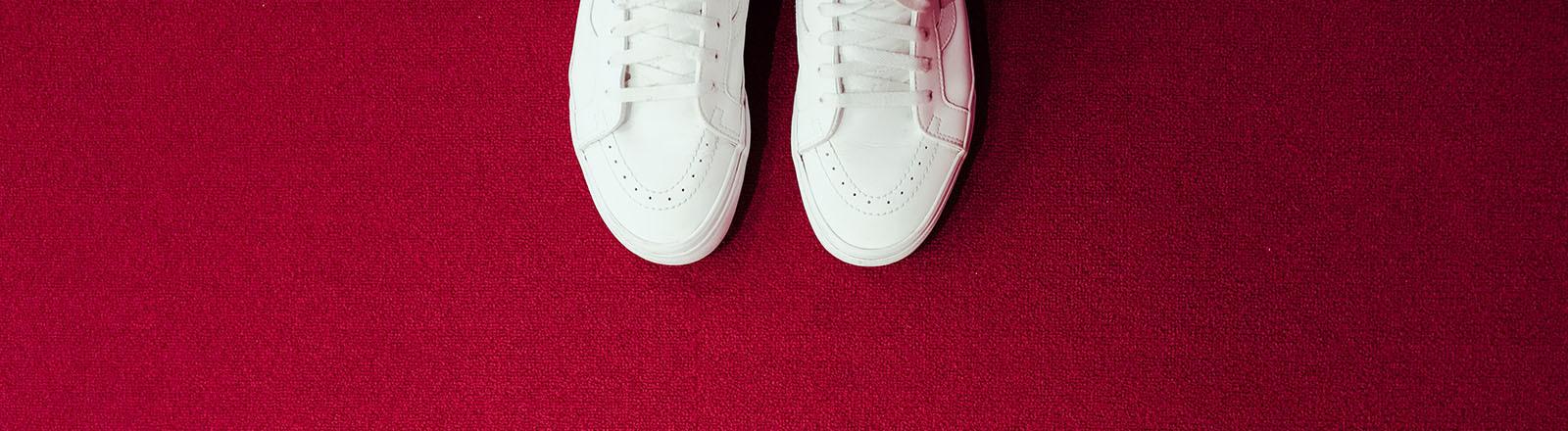 Weiße Sneaker stehen auf einem roten Teppich. Die Kamera blickt von oben auf die Sneaker.