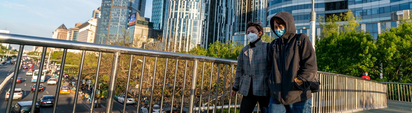 In Peking laufen zwei Personen über eine Fußgängerbrücke über eine mehrspurige Straße. Beide tragen Mundschutz (23.04.2020)