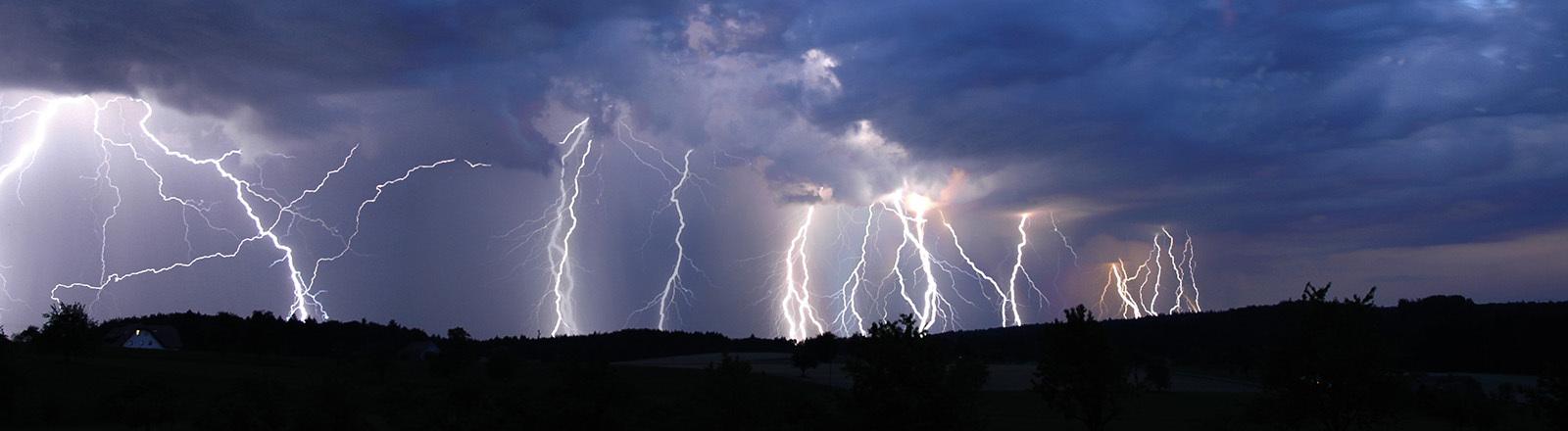 Ein Gewitter am Nachthimmel mit vielen Blitzen am Horizont.