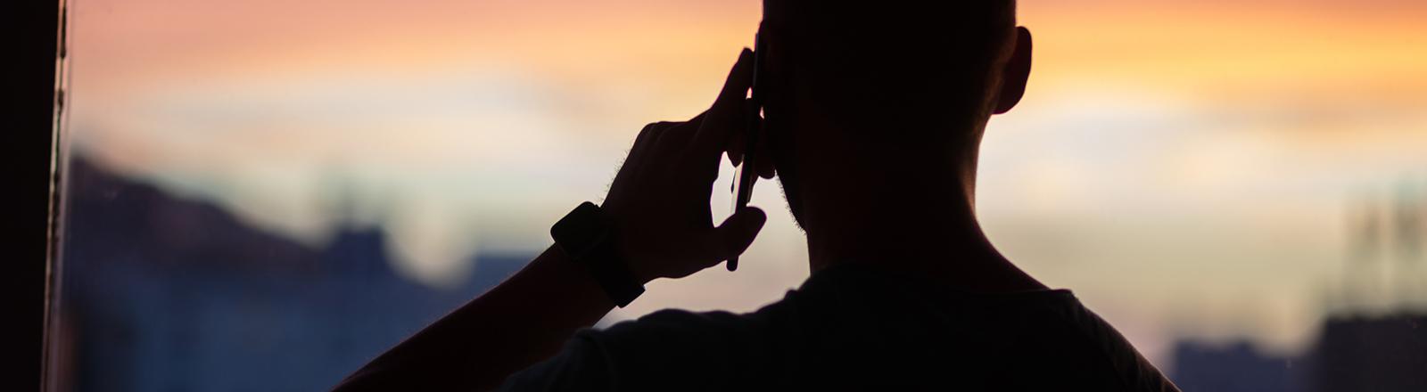 Ein Mann steht am offenen Fenster und telefoniert mit dem Handy; der Abendhimmel ist rot-blau gefärbt.