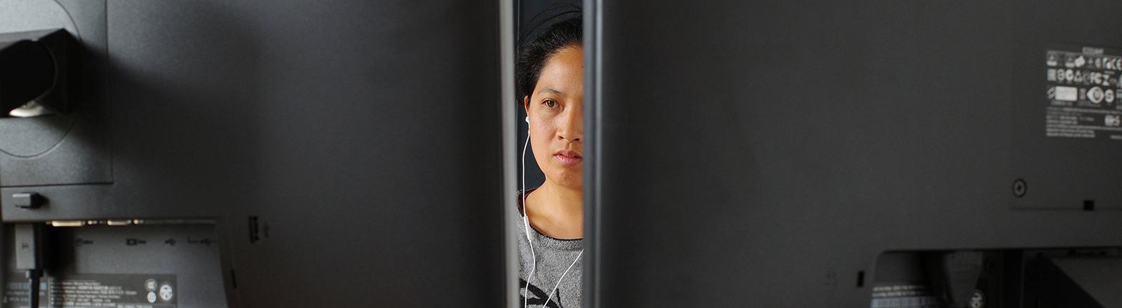 Eine Frau sitzt hinter zwei Computer-Bildschirmen.