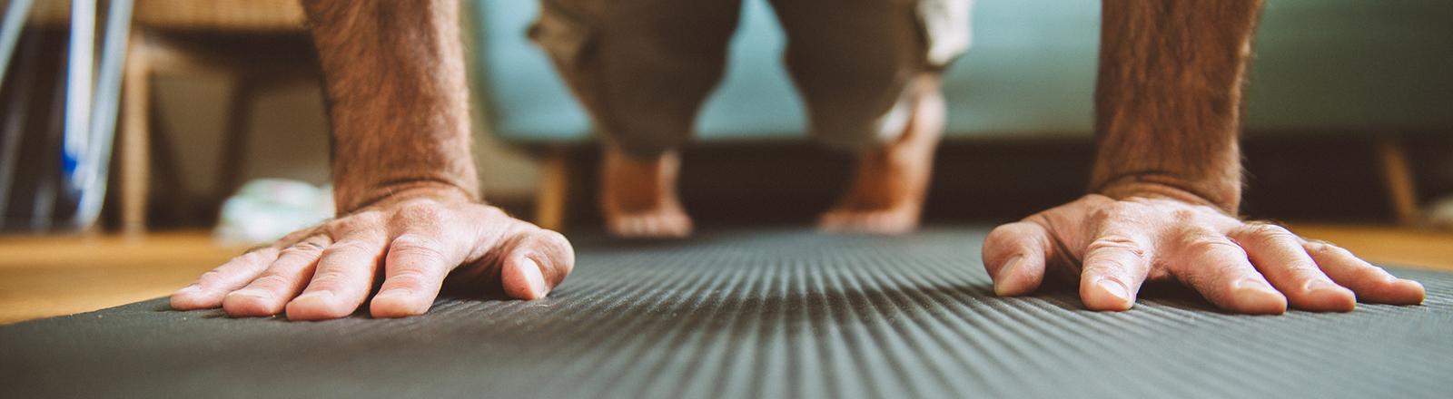 Ein Mann macht zu Hause auf einer Matte Liegestütze; man sieht nur seine Hände und seine Beine und Füße.