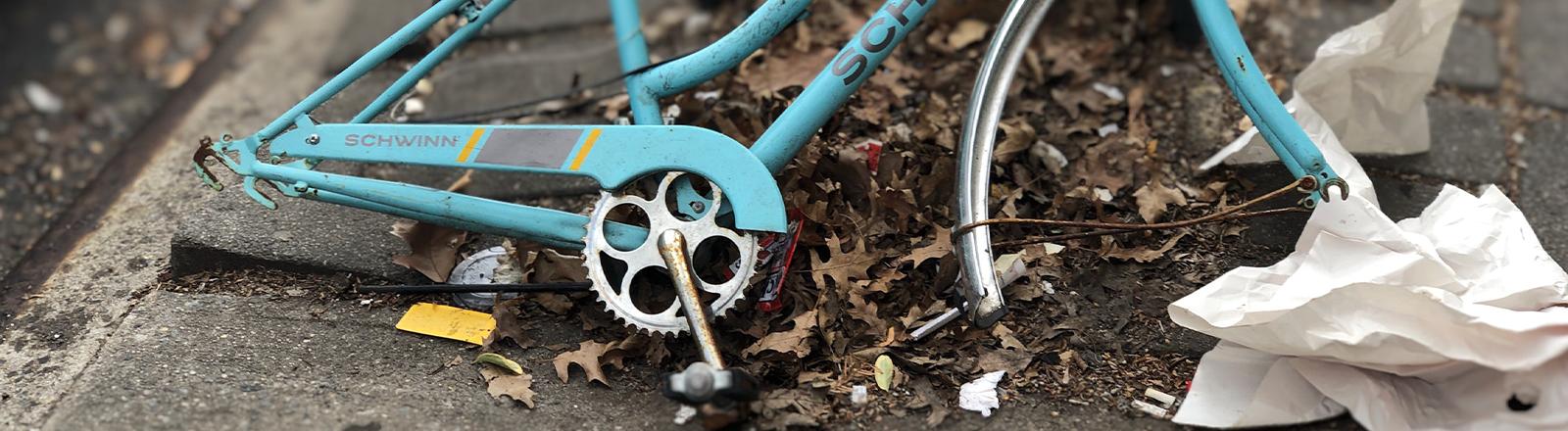 Ein Fahrrad angekettet an ein Gitter, es fehlen beide Räder, der Sattel und die Kette.